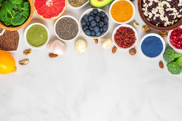 Gesunde vegane lebensmittel saubere essauswahl: obst, gemüse, samen, superfood, nüsse, beeren auf weißem marmorhintergrund. draufsicht mit kopierraum