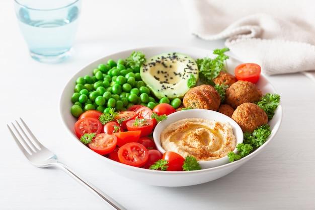 Gesunde vegane lunch bowl mit falafel hummus tomaten avocado erbsen