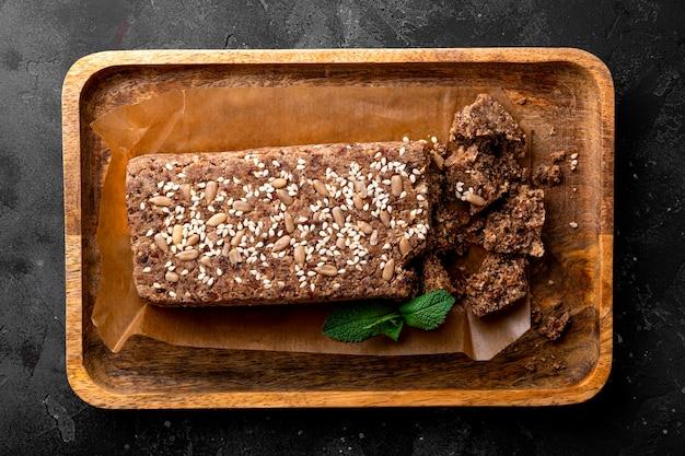 Gesunde vegane süßigkeiten zuckerfreie nüsse halva mit samen und sesam auf dem holzteller und dunkelgrau