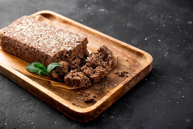 Gesunde vegane süßigkeiten zuckerfreie nüsse halva mit samen und sesam auf der holzplatte und dunkelgrau