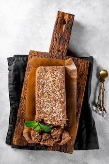 Gesunde vegane süßigkeiten zuckerfreie nüsse halva mit samen und sesam auf einem hölzernen schneidebrett draufsicht