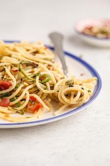Gesunde vegane teigwaren mit zucchini, tomaten und nüssen.