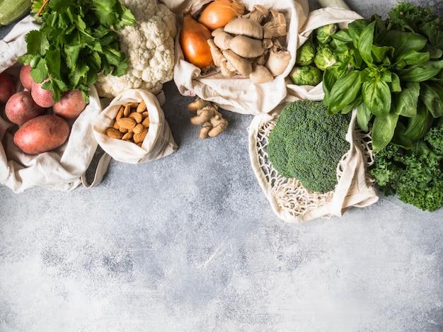 Gesunde vegane zutaten zum kochen. verschiedene saubere gesunde gemüse und kräuter in geflochtenen beuteln. produkte vom markt ohne kunststoff. null-abfall-konzept flach zu legen. kopieren sie platz