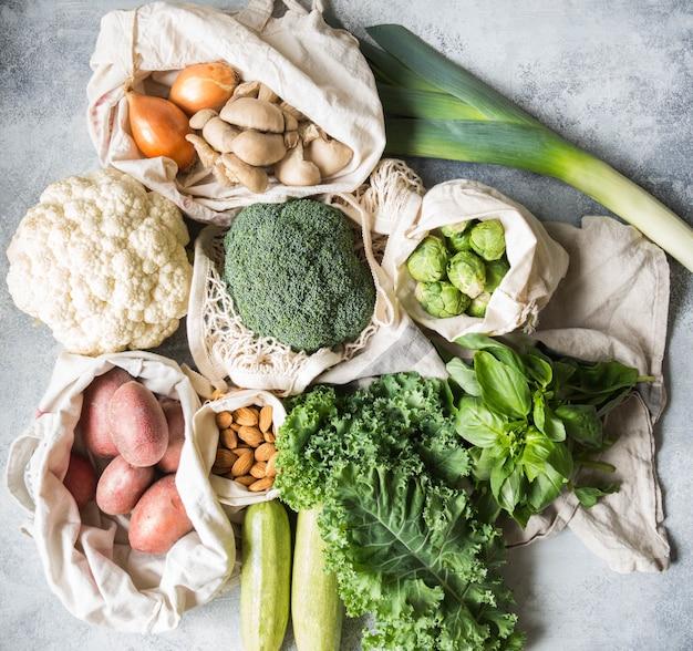 Gesunde vegane zutaten zum kochen. verschiedene saubere gesunde gemüse und kräuter in geflochtenen beuteln. produkte vom markt ohne kunststoff. null-abfall-konzept