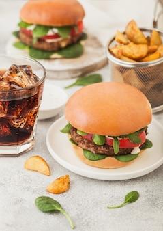 Gesunde vegetarische fleischfreie burger auf rundem keramikteller mit gemüse auf leuchttisch mit kartoffelschnitzen und glas cola.