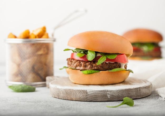 Gesunde vegetarische fleischfreie burger auf rundem schneidebrett mit gemüse auf hellem hintergrund mit kartoffelschnitzen.