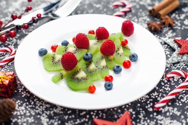 Gesunde weihnachtsdessert snack frühstück kiwi weihnachtsbaum von blaubeeren und himbeeren