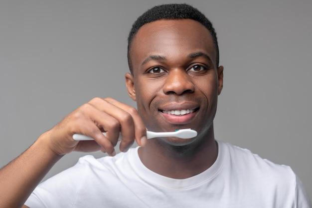 Gesunde zähne. fröhlicher attraktiver afroamerikaner mit zahnbürste in der nähe von lächelndem mund auf hellgrauem hintergrund