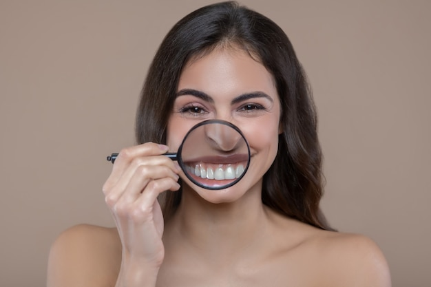 Gesunde zähne. junge fröhliche frau mit entblößten schultern, die lupe nahe lächelndem mund halten, der vergrößerte weiße zähne zeigt