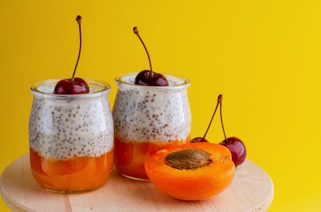 Gesunde zuckerfreie chia puddings mit zertrümmerter aprikose und süßer kirsche auf gelb.