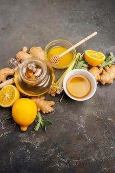 Gesunden antioxidans- und entzündungshemmenden ingwertee mit frischem ingwer, zitronengras, salbei, honig und zitrone auf dunklem hintergrund mit kopienraum machen.