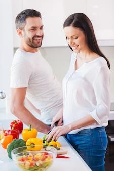 Gesunden lebensstil genießen. schöne junge und fröhliche frau, die in der küche gemüse schneidet, während ihr mann in ihrer nähe steht und lächelt