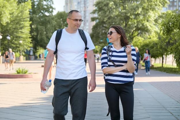 Gesunder aktiver lebensstil von älteren menschen, paar mittleren alters in sportbekleidung, die im park spazieren gehen und sprechen