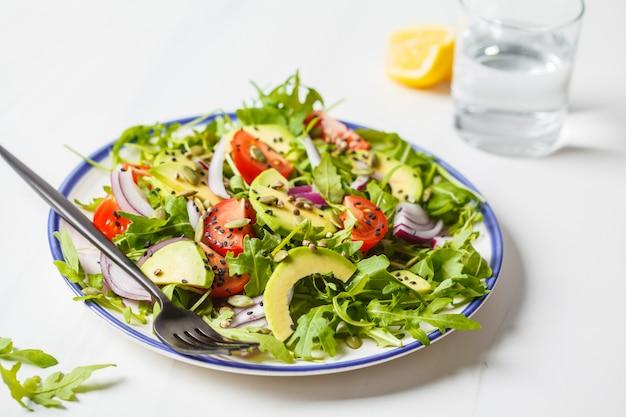 Gesunder arugula, avocado, tomatensalat auf weißem marmorhintergrund.