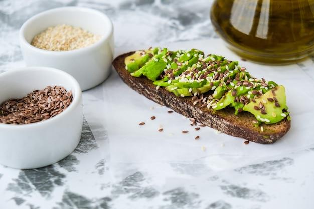 Gesunder avocado-toast auf konkretem hintergrund. vollkornbrot, sesam-leinsamen-olivenöl. vegane ketogene ernährung. gesundes essen. vegetarisch trendiges guacamole-sandwich.