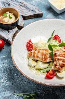 Gesunder caesar-salat mit gegrilltem hühnchen, käse und croutons, wachteleiern und kirschtomaten, köstliches ausgewogenes lebensmittelkonzept, vertikales bild. ansicht von oben. platz für text.