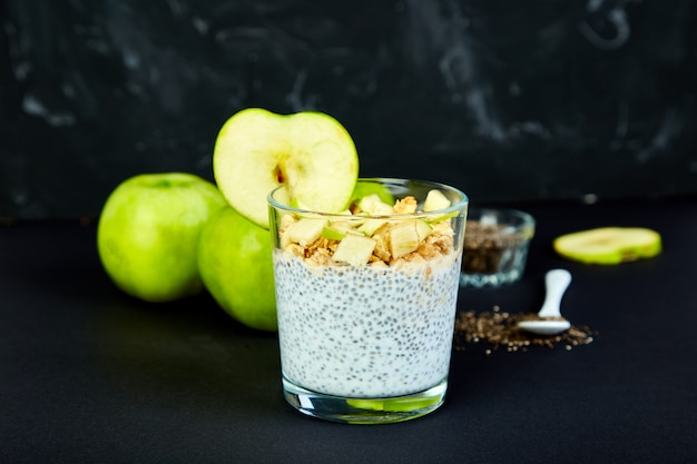 Gesunder chia pudding mit äpfeln und granola im glas.