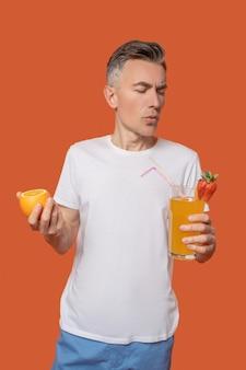 Gesunder cocktail. ernsthafter interessierter mann im weißen t-shirt mit fruchtcocktail und zitrusfrüchten in den händen auf orangefarbenem hintergrund