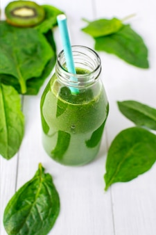 Gesunder detox-grün-smoothie mit kiwi- und spinatblättern in einer glasflasche mit strohhalm.