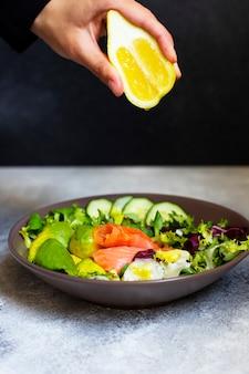 Gesunder diät-salat mit lachs, avocado, kürbiskernen, frischem gemüse und zitrone, serviert auf einem grauen tisch. weibliche hand drückt zitrone auf den salat. das konzept der gesunden ernährung. schwarzer hintergrund