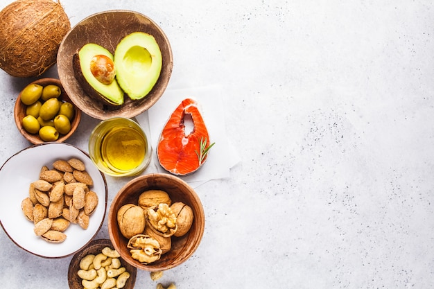 Gesunder fetter nahrungsmittelhintergrund. fische, nüsse, öl, oliven, avocado auf weißem hintergrund, draufsicht