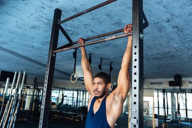 Gesunder fitness-mann macht liegestütze mit horizontaler stange im fitnessstudio