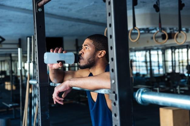 Gesunder fitness-mann trinkt wasser beim ausruhen im fitnessstudio