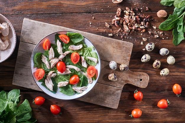 Gesunder frisch zubereiteter salat aus wachteleiern, fleisch, tomaten und spinat in einem teller auf einem holzbrett auf dem küchentisch. diätetisches mittagessen. flach liegen