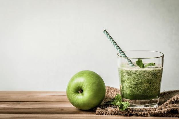 Gesunder frischer grüner smoothiesaft in der glasflasche auf holztisch