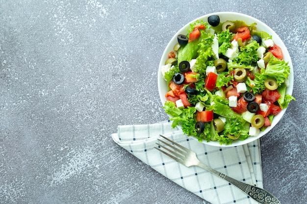 Gesunder frischer salat mit salat, oliven, tomaten- und feta-käse, gabel
