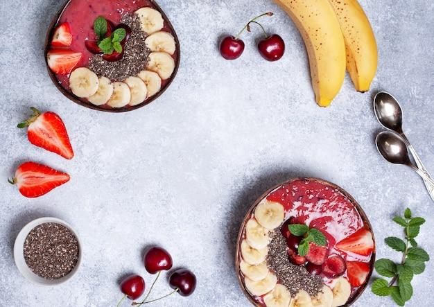 Gesunder frühstück smoothieschüsselhintergrund mit copyspace. ansicht von oben