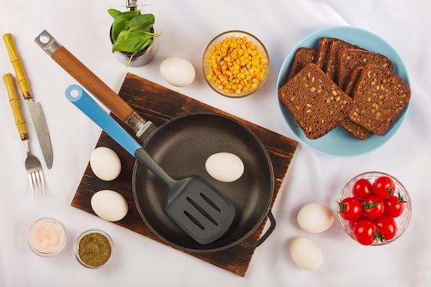 Gesunder frühstückshintergrund mit eiern, kräutern, kirschtomaten und dunklem brot