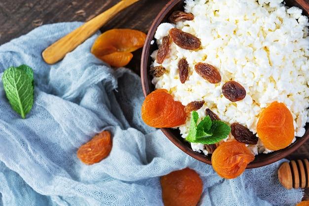 Gesunder frühstückshüttenkäse mit rosinen, getrockneten aprikosen, mandel, cashew und minze