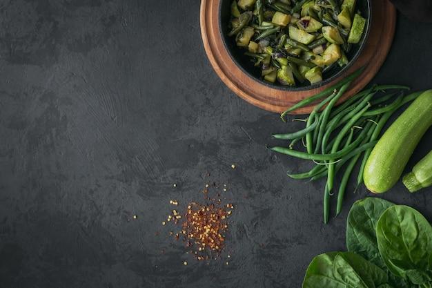 Gesunder frühstückstisch mit gebratenem gemüse in der pfanne und zutat zum kochen auf schwarzem kopierraum der draufsicht