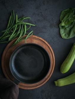 Gesunder frühstückstisch mit leerer kochpfanne und zutat zum kochen auf schwarzer draufsicht