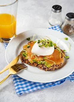Gesunder frühstückstoast mit avocado, lachs, pochiertem ei und microgreens in weißer platte. pescatrian diät. gehirnnahrung. omega-3-fette. hausmannskost