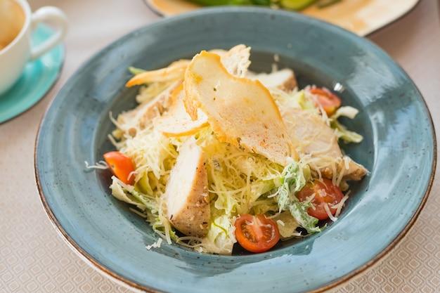 Gesunder gegrillter hühnchen-caesar-salat mit käse und croutons. caesar-salat mit croutons, wachteleiern