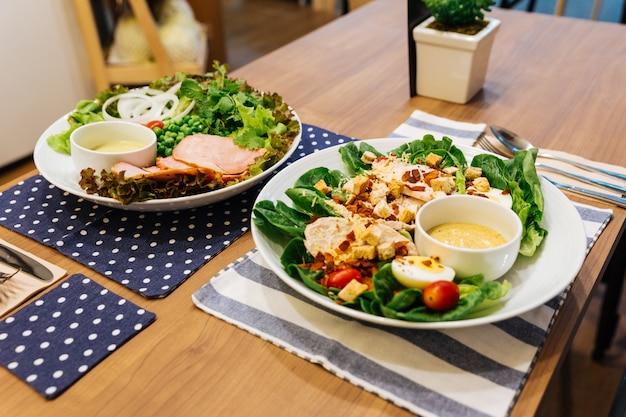 Gesunder gegrillter hühnercäsar-salat mit käse, croutons, grüner eiche, gekochtem ei und cris