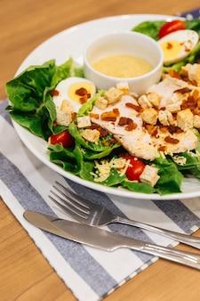 Gesunder gegrillter hühnercäsarsalat mit käse, croutons, grüner eiche, gekochtem ei
