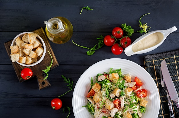 Gesunder gegrillter huhn-caesar-salat mit tomaten, käse und croutons.
