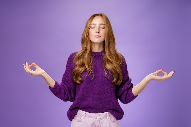 Gesunder geist im körper. friedliche und glückliche attraktive frau mit roten haaren und sommersprossen schließen die augen und lächeln aus ruhigen und erleichterten gefühlen, während sie in lotuspose mit mudra-geste meditieren und yoga machen.
