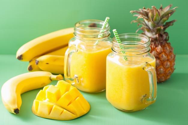 Gesunder gelber smoothie mit mango-ananas-banane in einmachgläsern