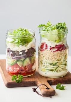 Gesunder gemüsekäsesalat in einmachgläsern