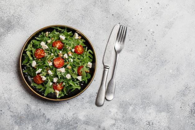 Gesunder gemüsesalat mit frischem rucola, tomate, feta und walnuss