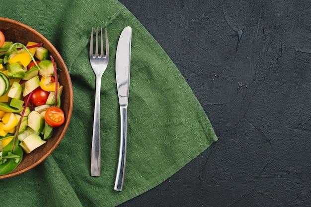 Gesunder gemüsesalat mit gabel und buttermesser auf tischdecke über schwarzem konkretem hintergrund