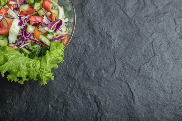 Gesunder gesunder videowinkel-bio-salat auf schwarzem hintergrund. hochwertiges foto