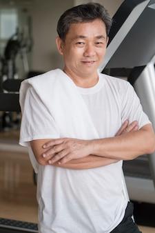 Gesunder, glücklicher, lächelnder, positiver älterer wohlbefinden asiatischer mann, der im fitnessstudio trainiert