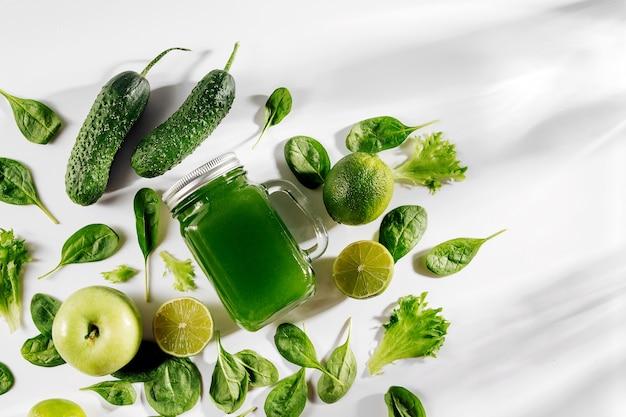 Gesunder grüner gemüsesaft mit spinat und grünem obst und gemüse auf weißem tisch.