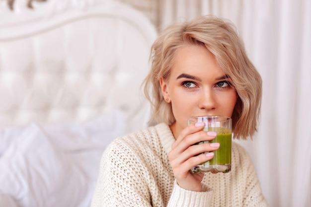 Gesunder grüner saft. nahaufnahme einer blonden jungen frau, die gesunden grünen saft im schlafzimmer trinkt