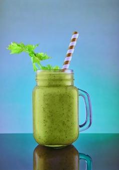 Gesunder grüner smoothie, gesunde ernährung, lebensstil, veganes, alkalisches, vegetarisches konzept. grüner smoothie mit bio-zutaten, gemüse auf blau